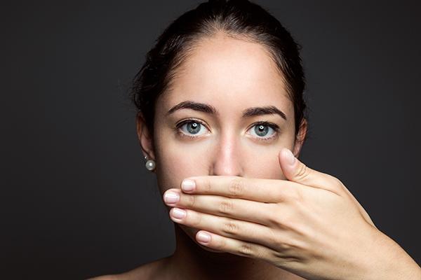 Eliyle ağzını kapayan kız